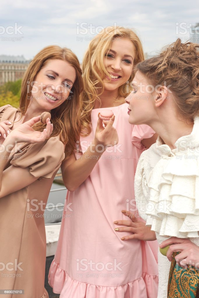 Young fashion ballerinas in colourful dresses want to taste a sweet macaroons stock photo