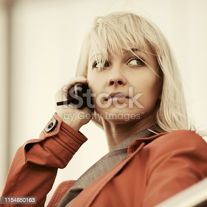 Young fashion blond business woman wearing red jacket calling on cell phone on city street