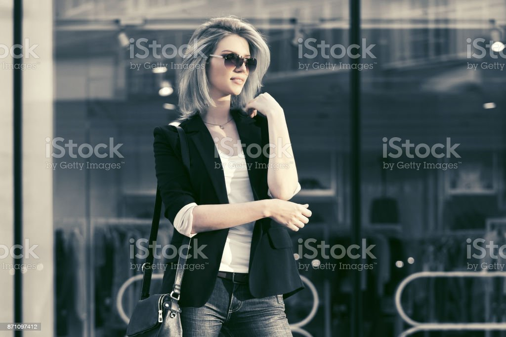 Young fashion blond business woman in sunglasses at the mall stock photo