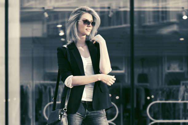 junge mode blond business-frau mit sonnenbrille in der mall - handtasche jeans stock-fotos und bilder