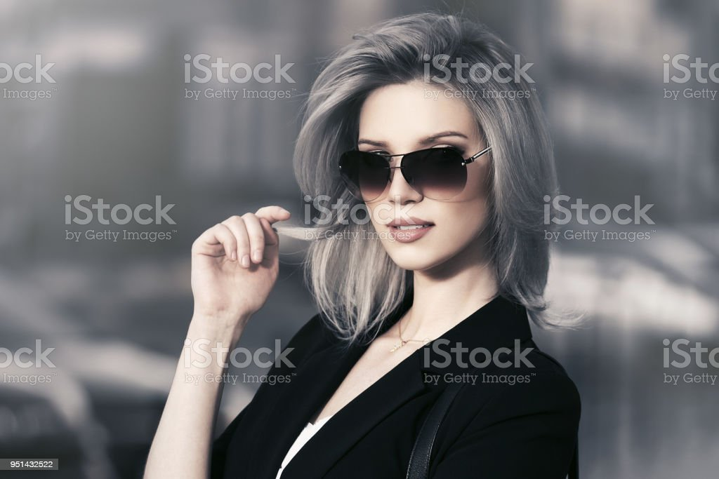 Young fashion blond business woman in sunglasses walking in city street stock photo