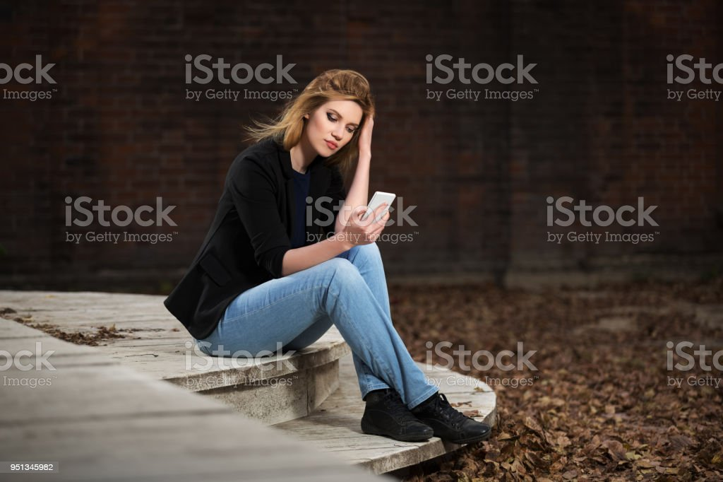 Young fashion blond business woman using smart phone in city street stock photo