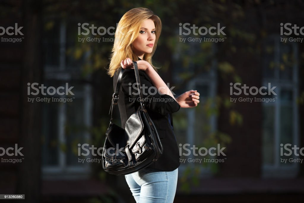 Young fashion blond business woman with handbag walking in night on city street stock photo