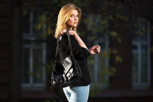 young fashion blond business-frau mit handtasche wandern in nacht auf stadtstraße - handtasche jeans stock-fotos und bilder