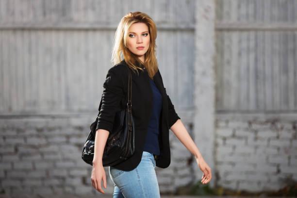 young fashion blond business-frau mit handtasche zu fuß auf stadtstraße - handtasche jeans stock-fotos und bilder