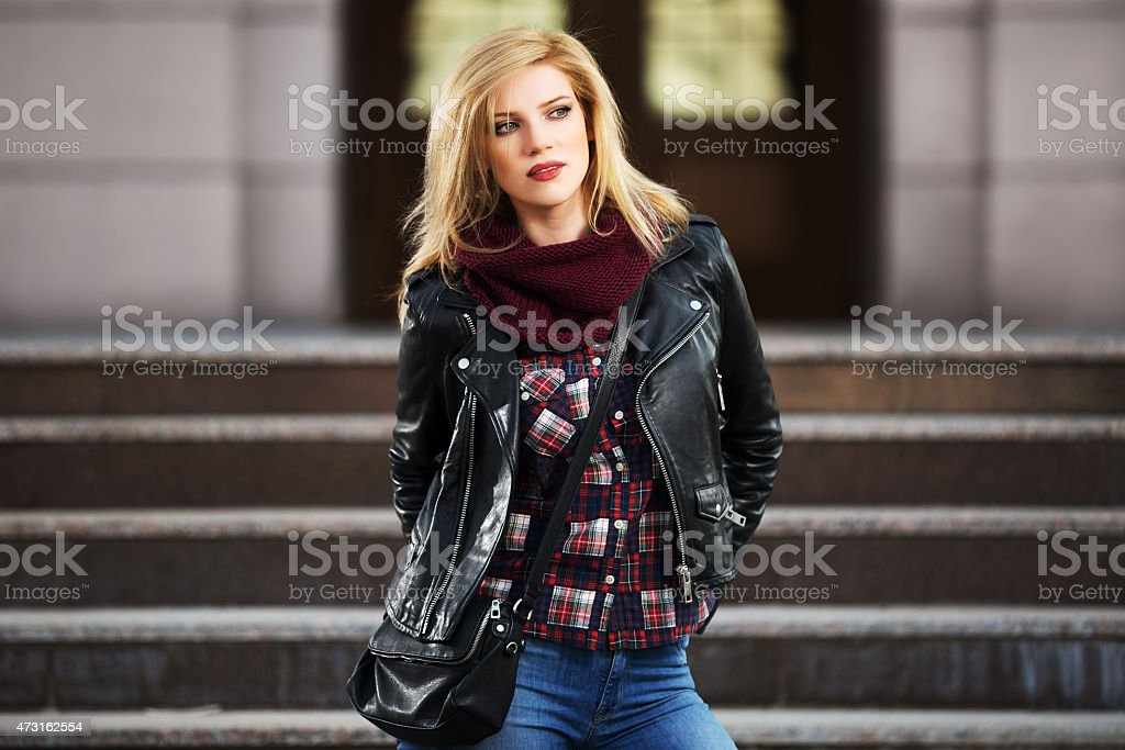 Young fashion blond woman in leather jacket on the steps stock photo