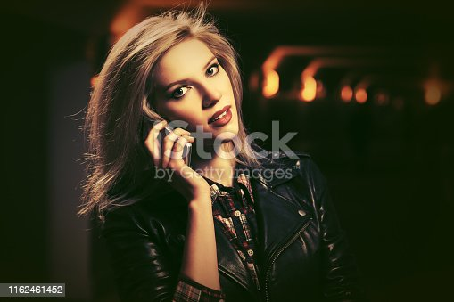Young fashion blond woman talking on cell phone on night city street Stylish female model with bob hair wearing black leather jacket
