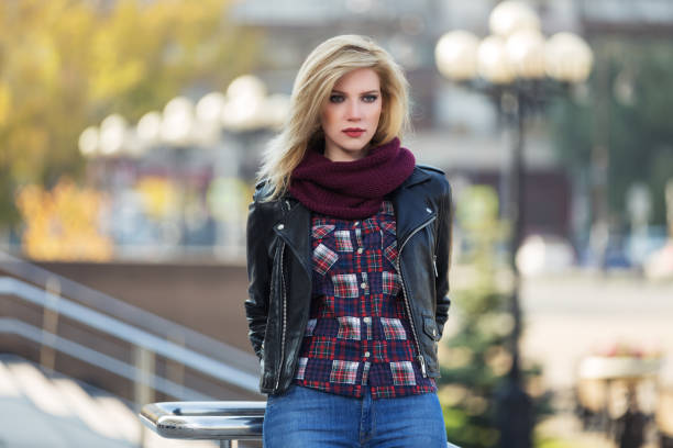 Young fashion blonde woman in black leather jacket and snood scarf