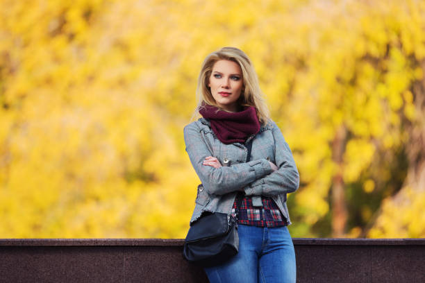 Young fashion blonde woman in checked plaid blazer and snood scarf