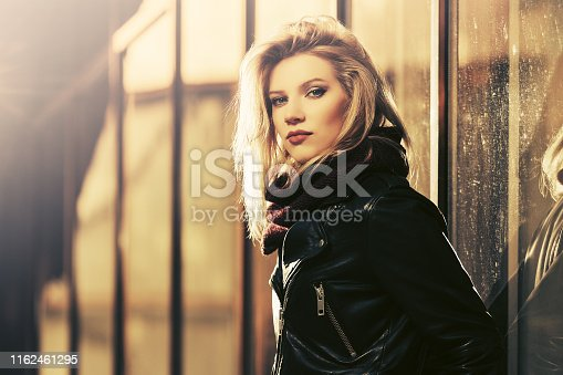 Young fashion blonde woman wearing black leather jacket and brown scarf at the mall window