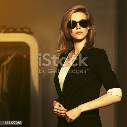 Young fashion blonde woman in sunglasses and black suit jacket in the mall interior
