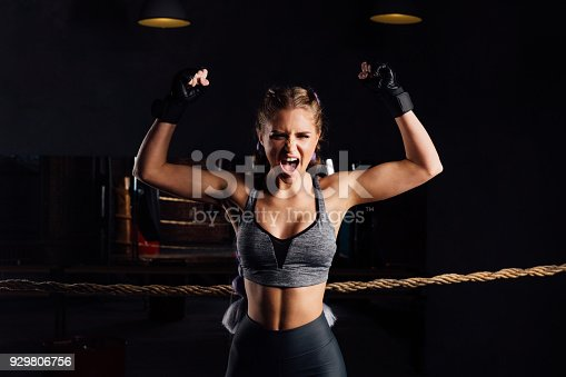istock Young fashion boxer girl with boxing gloves screams emotionally rising arms 929806756