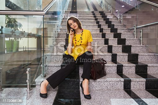 Young fashion business woman talking on cell phone in office interior Stylish fashion model in yellow blouse and black pants
