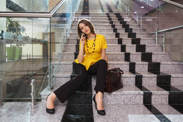 Young fashion business woman talking on cell phone in office interior