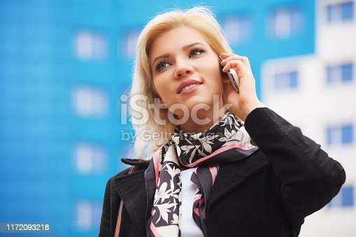 Young business woman talking on cell phone walking on city street  Stylish fashion model wearing black coat and silk scarf