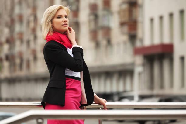 junge mode-business-frau zu fuß auf der stadtstraße - rote bleistiftröcke stock-fotos und bilder