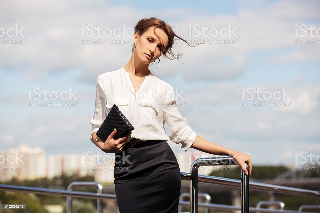 Young fashion business woman with handbag on the city street stock photo