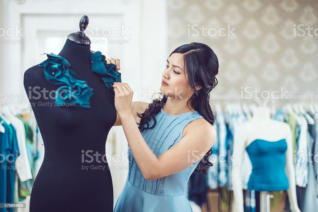 Young fashion designer is working in her showroom stock photo