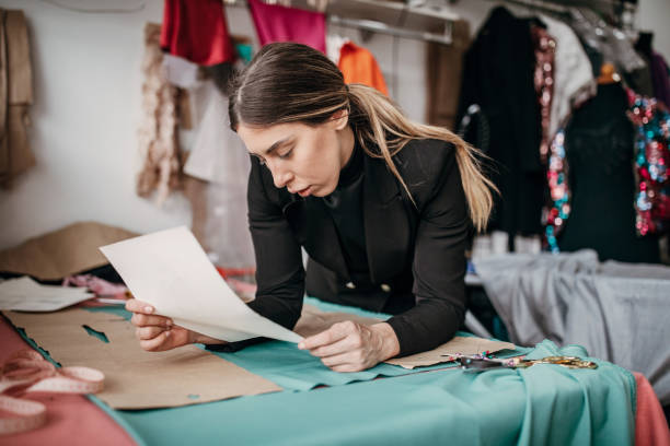 Young Fashion Designer Looking At New Dress Sketch Stock Photo Download Image Now Istock