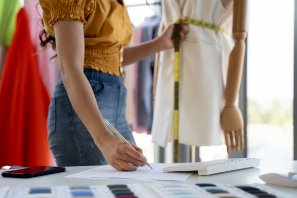 Young fashion designer working in her atelier stock photo