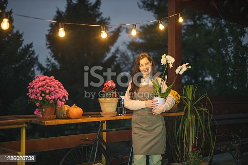 istock Young fashion female florist enjoying in her flower shop 1286020739