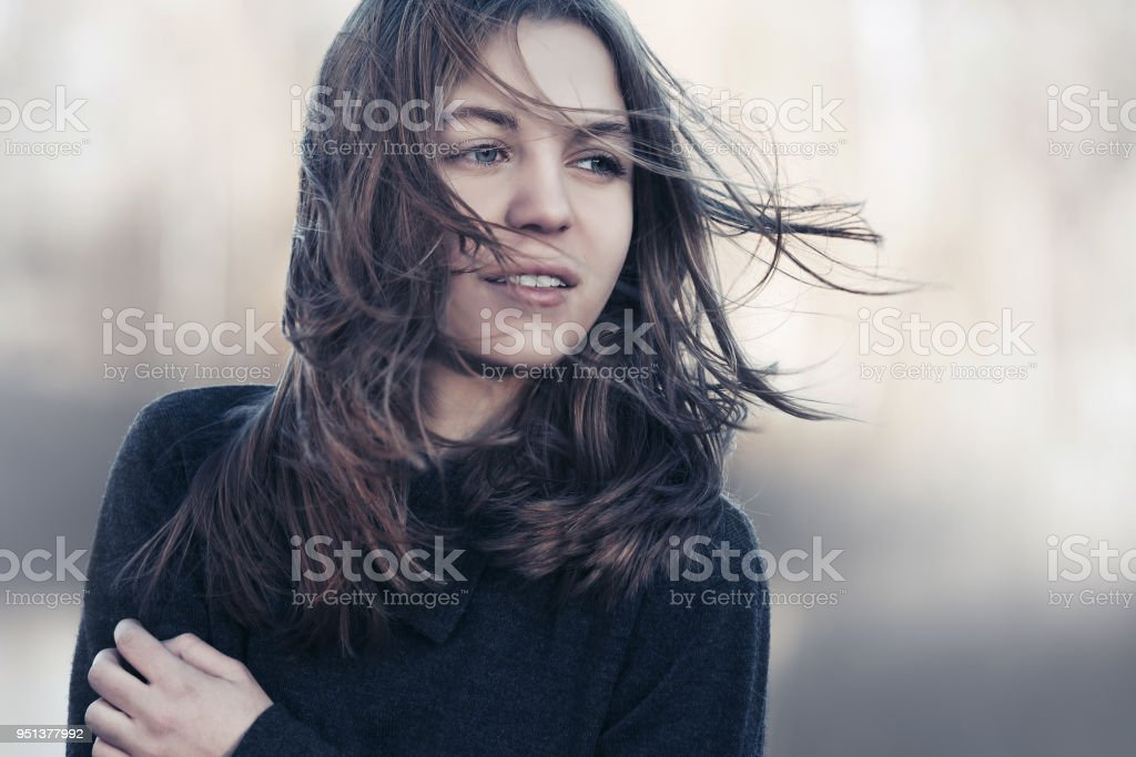 Young fashion girl in black sweater walking outdoor stock photo