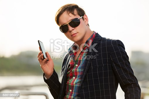 907934274 istock photo Young fashion man in sunglasses with a mobile phone outdoor 535195027