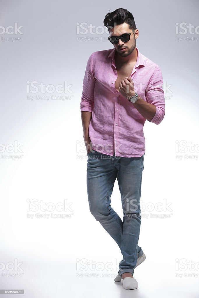 young fashion man with crossed feet and hand on shirt royalty-free stock photo