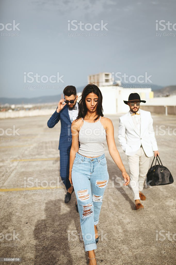 Young fashion model and two bodyguards stock photo