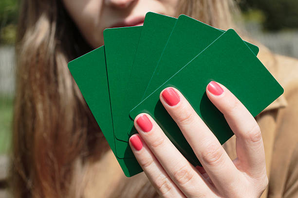 red nails against green playing cards latvian girl outdoors - whiteway polish outdoor girl stock photos and pictures