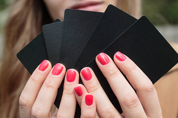 red nails against black playing cards latvian girl outdoors - whiteway polish outdoor girl stock photos and pictures