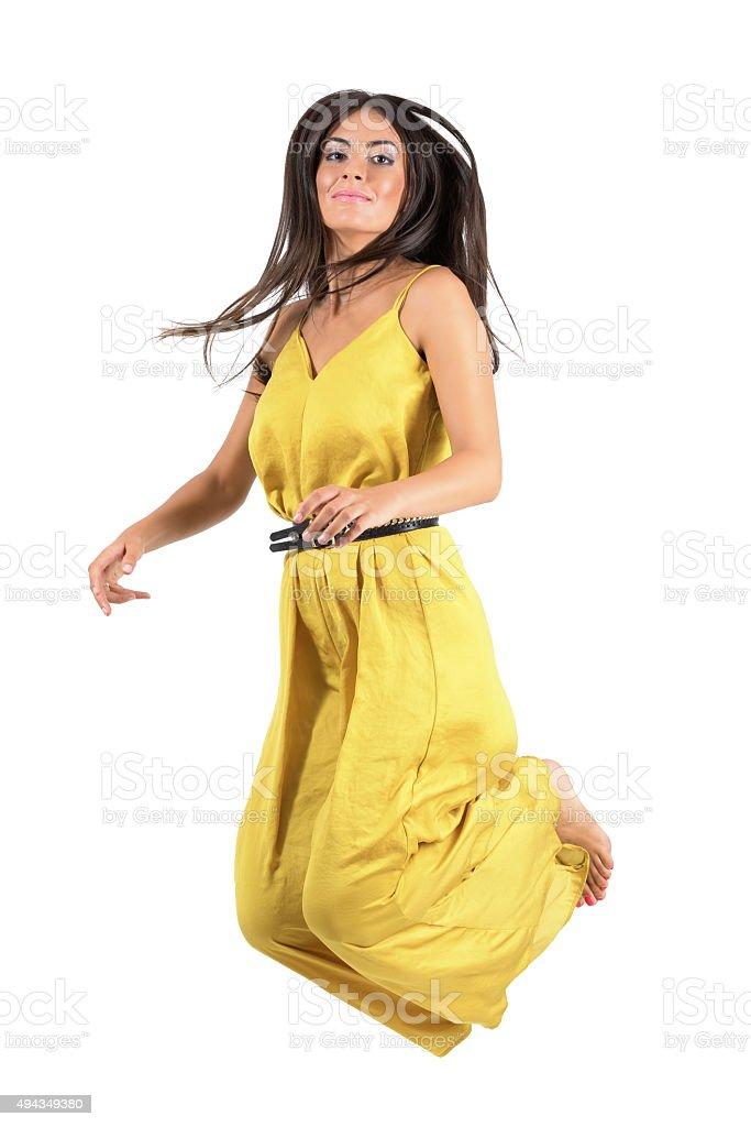 b50e2c0fd0 Modelo de moda joven en vestido amarillo jumps in mid aire. foto de stock  libre