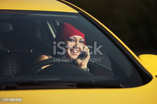Young fashion woman in red beanie calling on cell phone driving a car