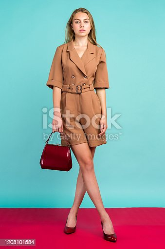539468216 istock photo Young fashion woman hold handbag clutch isolated on blue background 1208101584