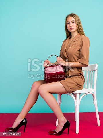 539468216 istock photo Young fashion woman hold handbag clutch isolated on blue background 1211824689