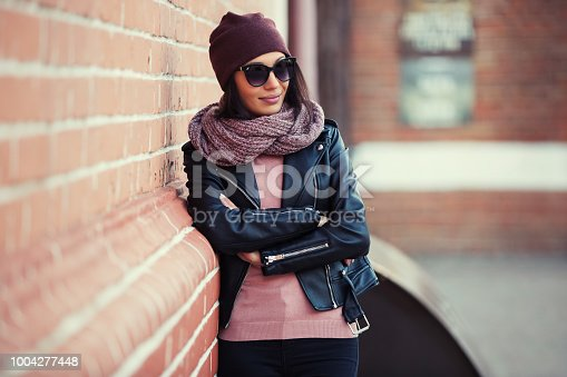 istock Young fashion woman in black leather jacket and sunglasses leaning on brick wall 1004277448