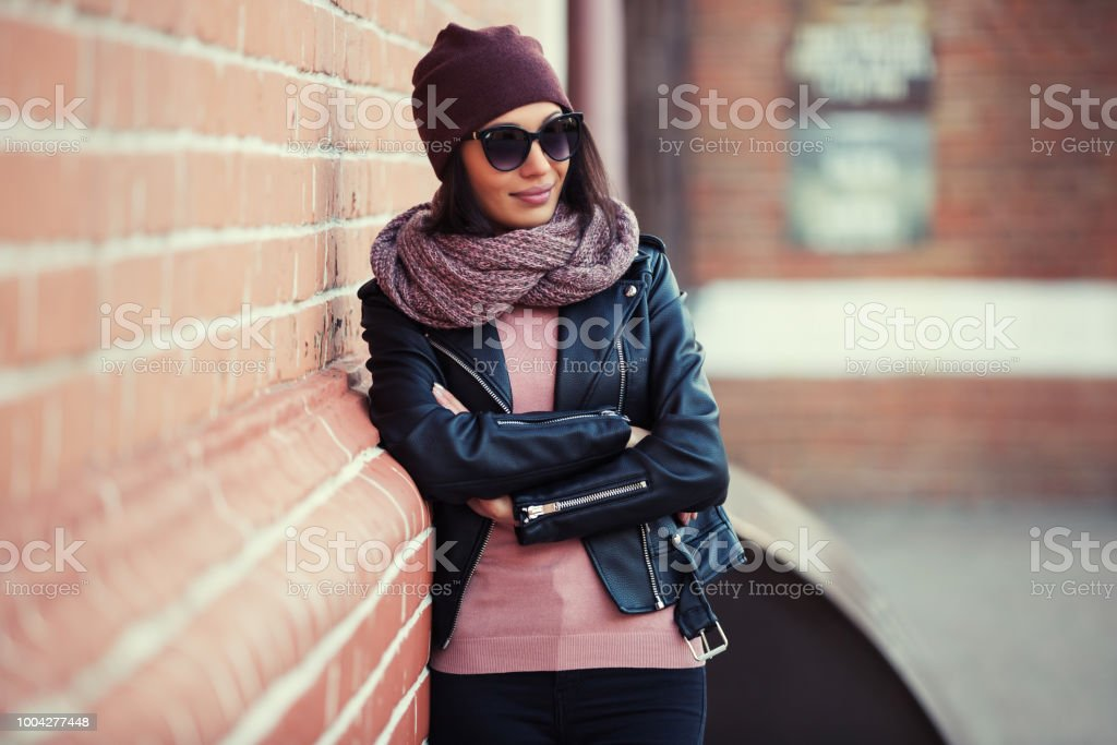 Young fashion woman in black leather jacket and sunglasses leaning on brick wall stock photo