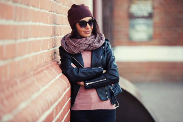 moda joven mujer chaqueta de cuero negra y gafas de sol, apoyado en la pared de ladrillo - moda de invierno fotografías e imágenes de stock