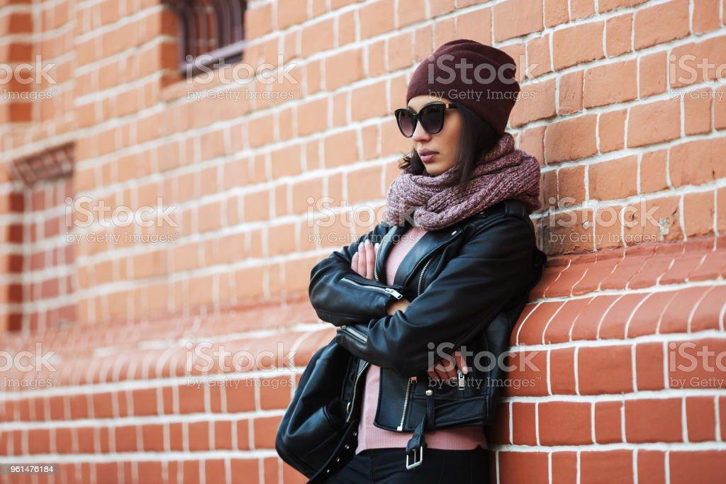 Sur Noir Femme En Jeune Le Blouson De Cuir Mur Mode Sappuyant wg86Px6q4