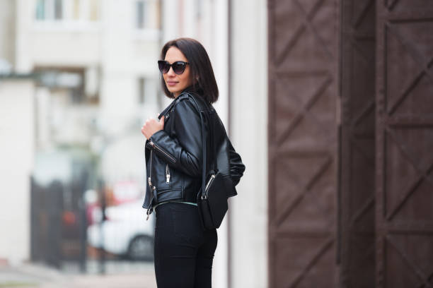 Young fashion woman in black leather jacket walking in city street Young fashion woman with handbag walking in city street Stylish female model in sunglasses and black leather jacket outdoor leather jacket stock pictures, royalty-free photos & images