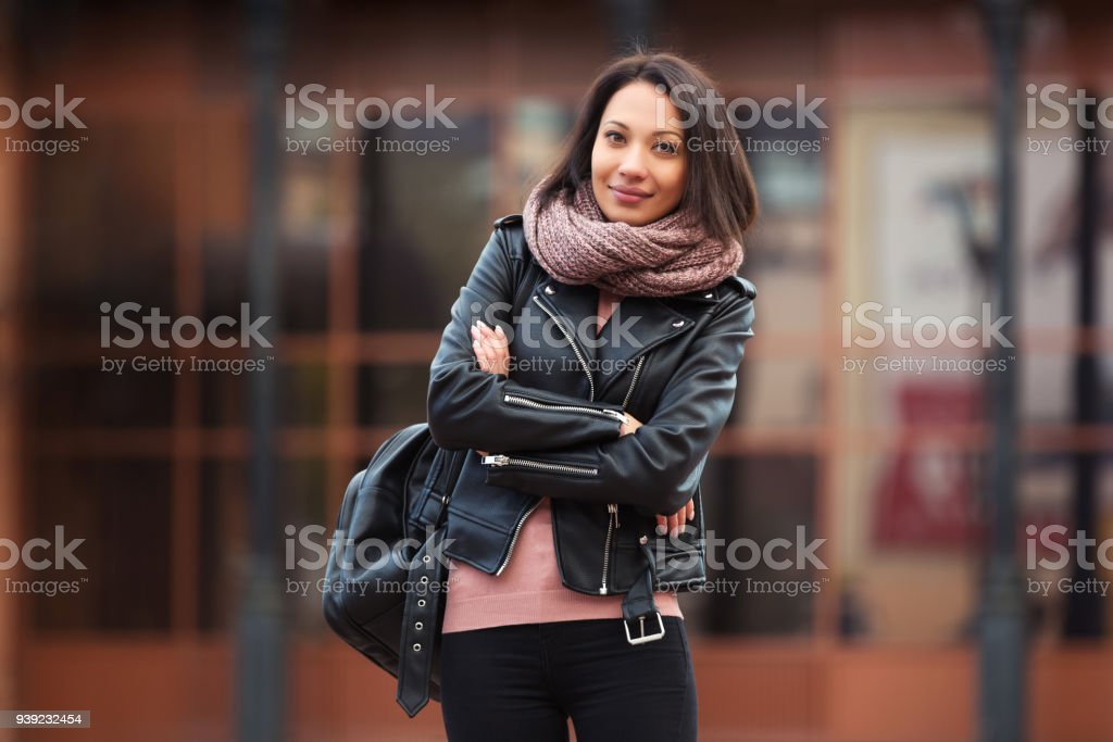 Young fashion woman in black leather jacket walking in city street stock photo