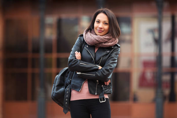 Young fashion woman in black leather jacket walking in city street Young fashion woman with backpack walking in city street Stylish female model in black leather jacket outdoor warm clothing stock pictures, royalty-free photos & images