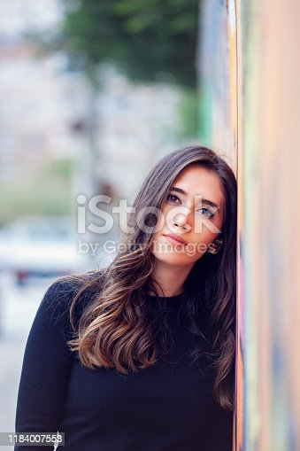 Young fashion woman in black sweatshirt leaning on colorful wall.