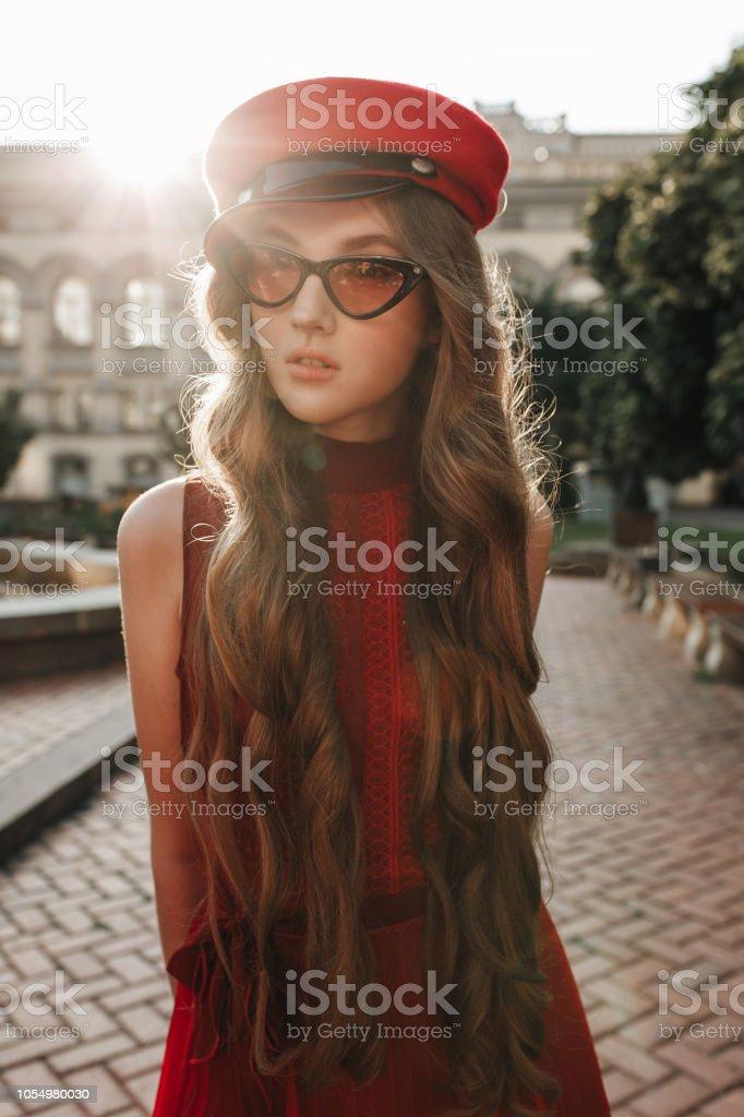 Junge Mode Frau In Lassigen Roten Kleid Hut Und Brille Uber Stadtische Hintergrund Herbst Portrat Hipster Madchen Posiert Auf Der Strasse Modische Lange Haarmodell In Eleganter Herbst Kleidung Stockfoto Und Mehr Bilder