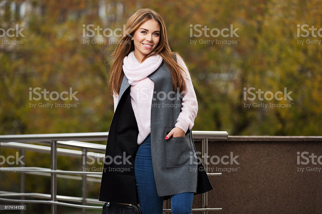 Young fashion woman in grey coat on city street stock photo