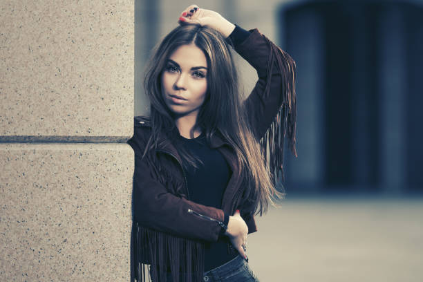 Young fashion woman in leather fringe suede jacket leaning on the wall