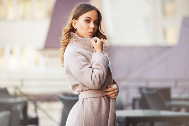 junge mode frau in hellen rosa mantel zu fuß in die stadt straße - winterjacke lang damen stock-fotos und bilder
