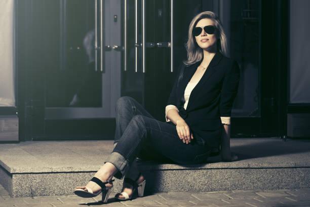junge mode-frau in sonnenbrille sitzt an der mall-tür - damen jeans sale stock-fotos und bilder