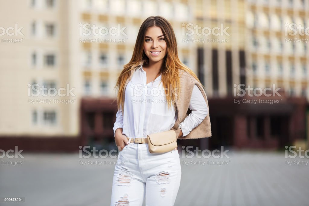 Young fashion woman in white shirt and ripped jeans walking in city street stock photo