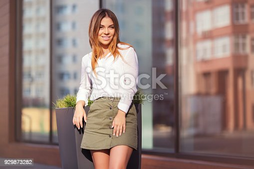 Young fashion woman standing next to mall window in a city street. Stylish female model in white shirt and short skirt outdoor